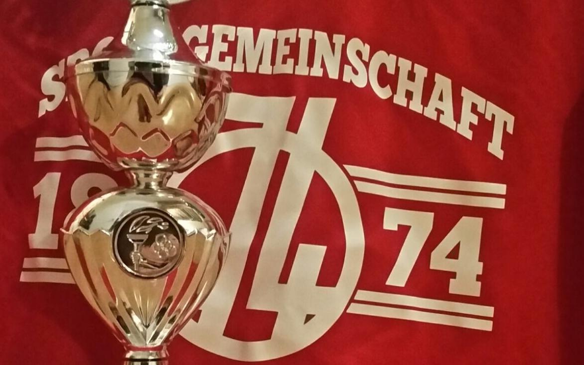 Pokal vor einem Pulli mit 74-Logo